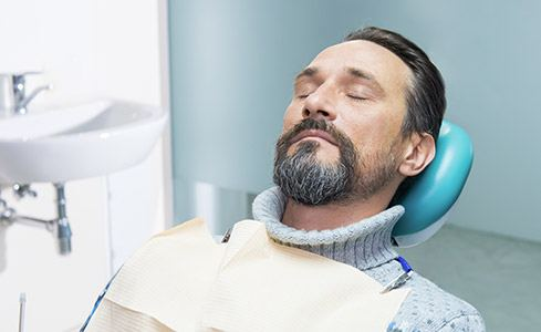 Man with eyes closed in dental chair