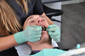 Man receiving oral cancer screening