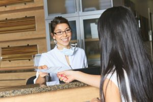 a person handing paperwork to a dental receptionist