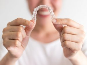 Smiling woman holding out Invisalign in Long Island City