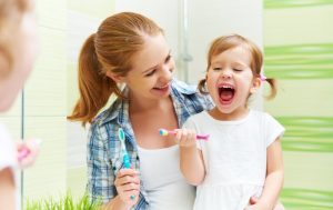 mother showing her daughter how to brush her teeth